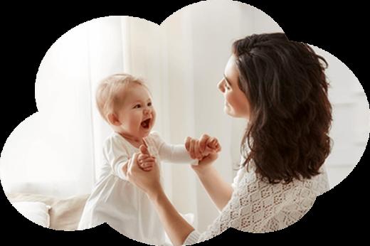Maman tenant son enfant debout par les mains.