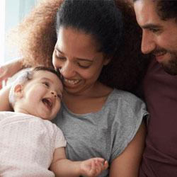 Un couple tenant un bébé dans ses bras.